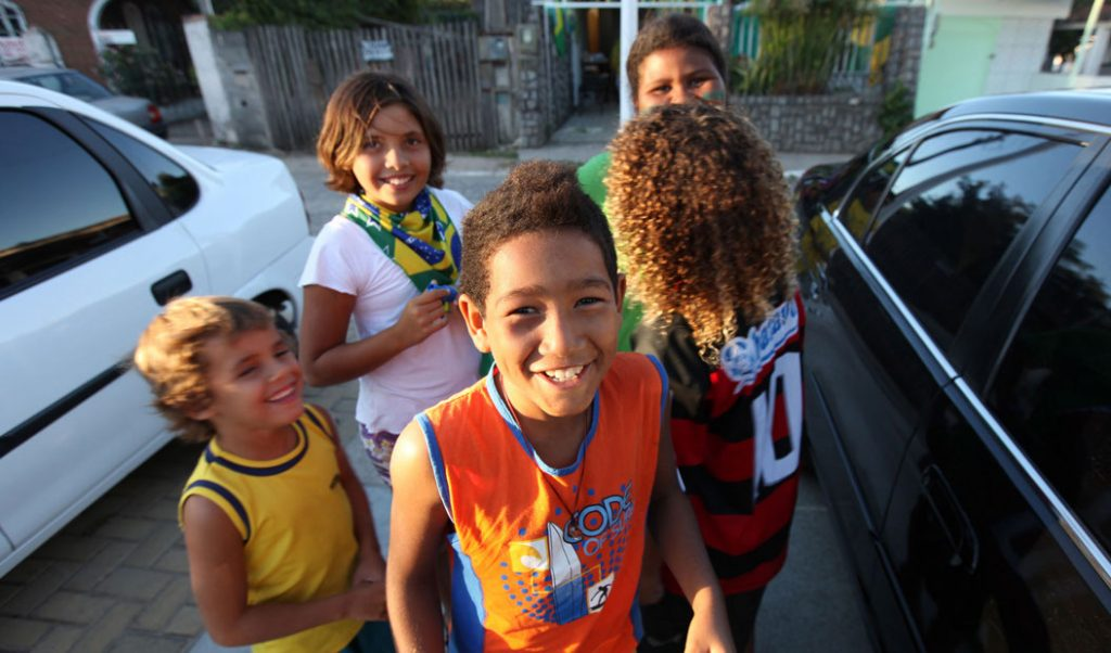children smiling near cars