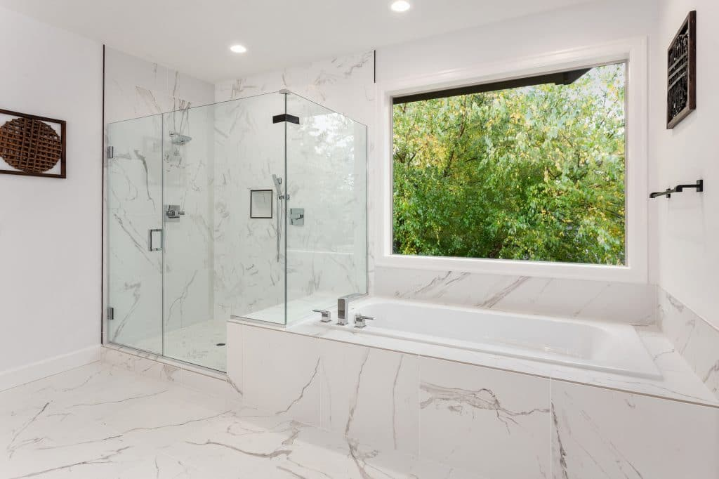 Master bathroom interior in new luxury home, with marble floor and wall accents. Shows large bathtub and shower. Shower walls are glass.